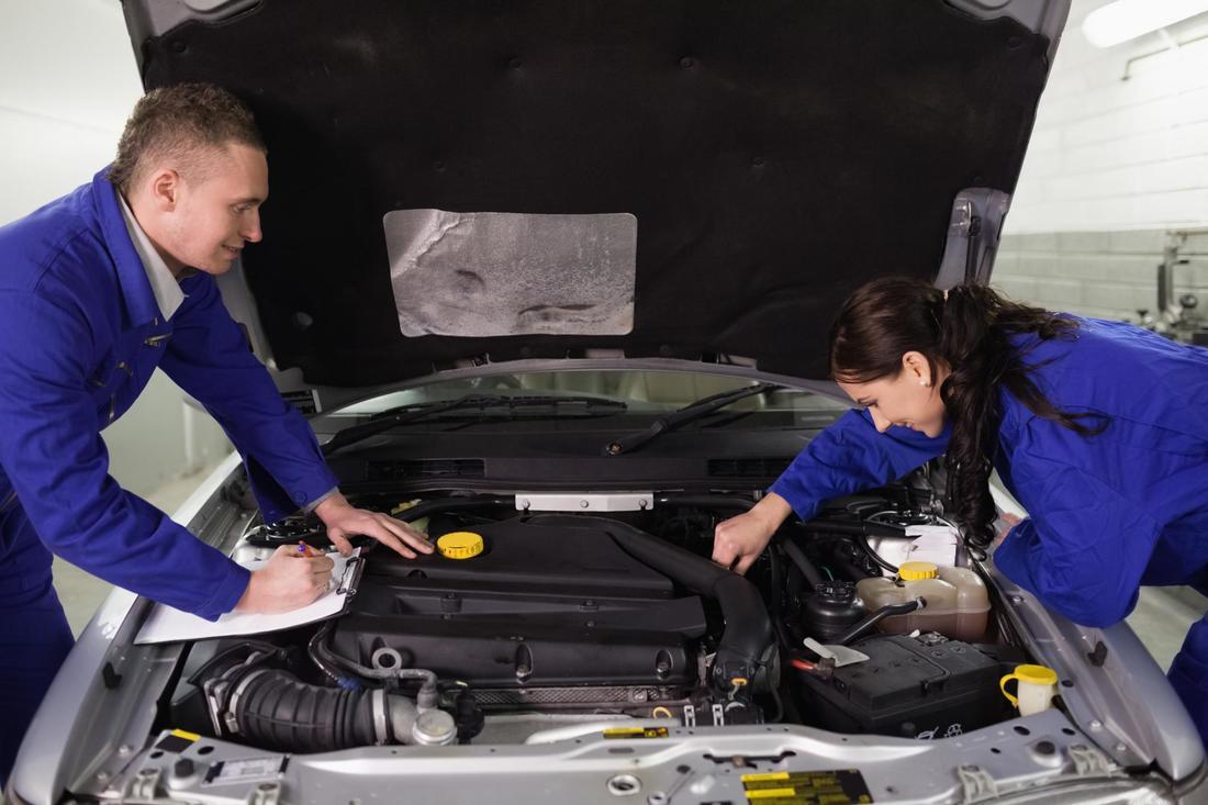 2 mechanics checking engine compartment